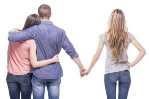 37921123 - love triangle. handsome man embrace his girlfriend while holding hands with another girl. isolated on white background.